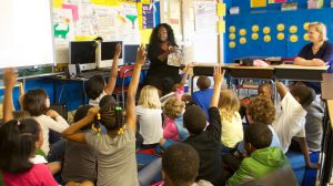 Children in classroom excitedly raising hands