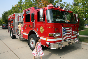 Little girl gazing in awe at a fire truck