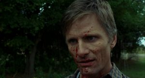 Viggo Mortensen as Tom Stall, with a blood-spattered face and haunted eyes