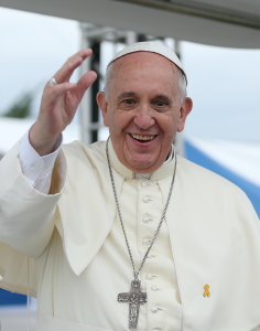 A smiling Pope Francis waves at the camera.